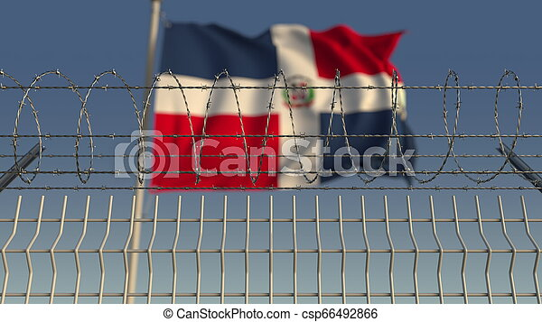 Blurred waving flag of the Dominican Republic behind barbed wire fence. 3D rendering - csp66492866