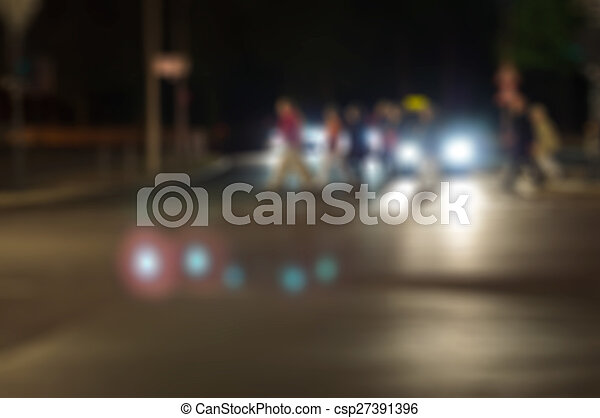 Blurry abstract cityscape night crosswalk with people - csp27391396