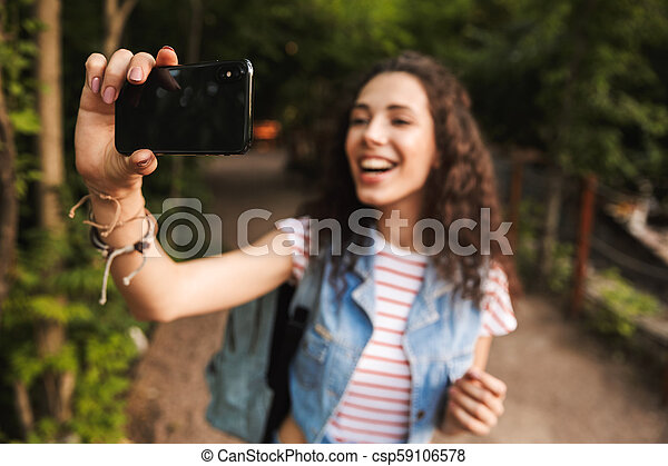 Blurry photo of brunette pretty woman 18-20 with backpack, smiling broadly and taking selfie photo on cell phone while walking along path in green park - csp59106578