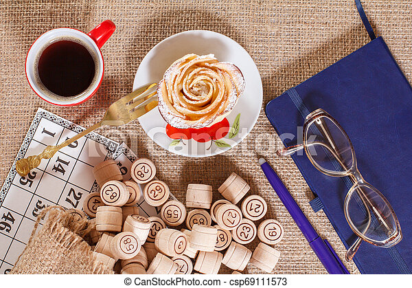 Board game lotto on sackcloth. Wooden lotto barrels in bag and game cards with notebook, pen, cup of coffee and homemade cookie. - csp69111573