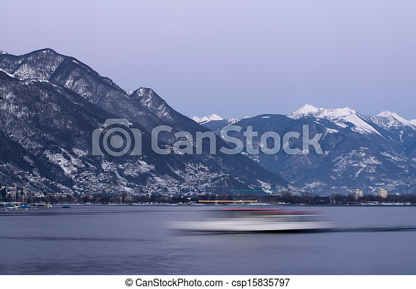 Boat and snow-capped mountains in blue hour - csp15835797