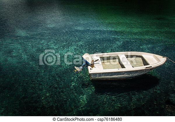 Boat in calm lake water. - csp76186480
