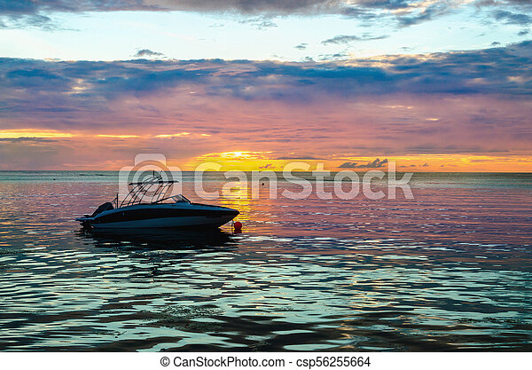 Boat in the ocean at sunset - csp56255664
