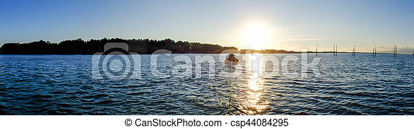 Boat in the ocean with sunset panorama - csp44084295