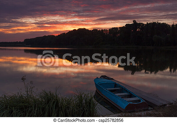 Boat near the shore of the lake at sunset - csp25782856