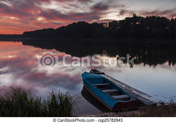 Boat near the shore of the lake at sunset - csp25782843