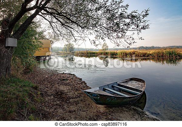 Boat on river at beautiful summer sunrise - csp83897116