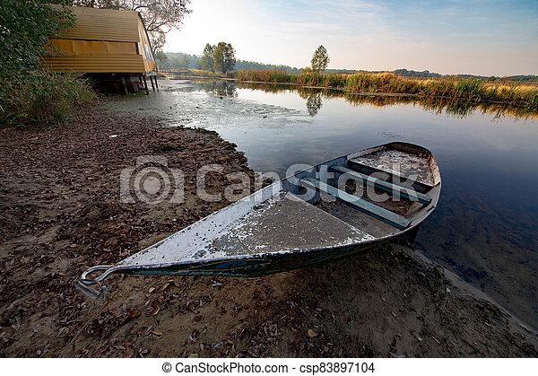 Boat on river at beautiful summer sunrise - csp83897104