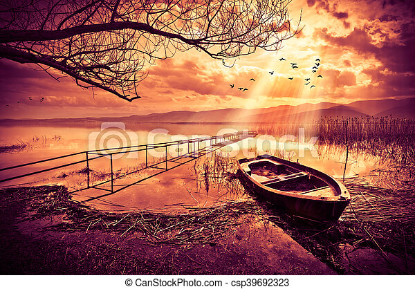 Boat on the lake at sunset - csp39692323