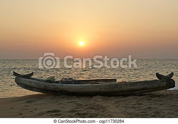boat on the ocean shore at sunset. Kerala, India - csp11730284