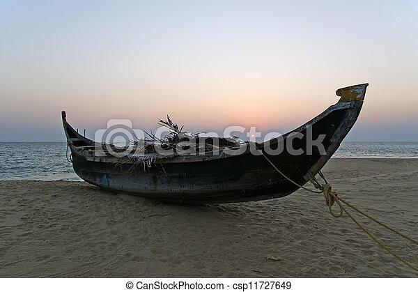 boat on the ocean shore at sunset. Kerala, India - csp11727649