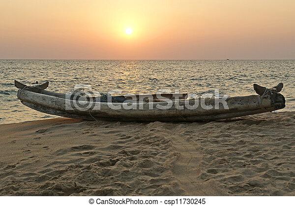 boat on the ocean shore at sunset. Kerala, India - csp11730245
