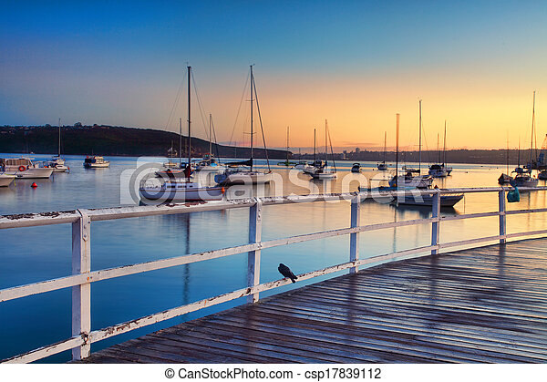 Boats moored bobbing in the waters at sunrise - csp17839112