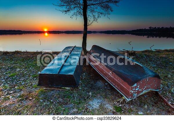 Boats on lake shore at sunset - csp33829624