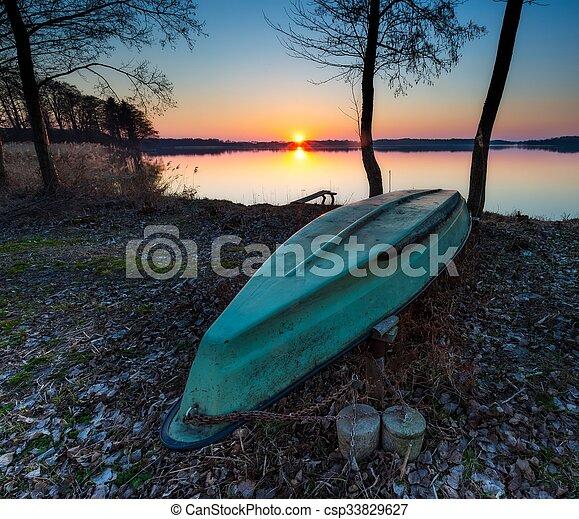Boats on lake shore at sunset - csp33829627