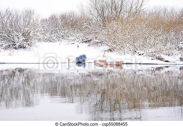 Boats on shore of winter river - csp55088455