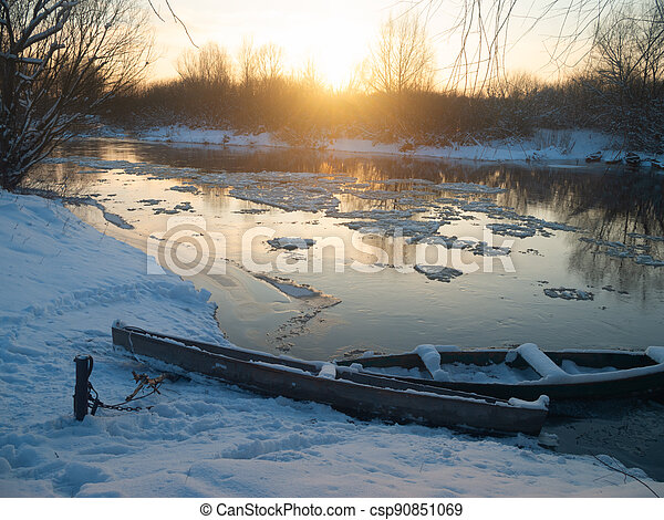 boats on the shore of the river winter - csp90851069