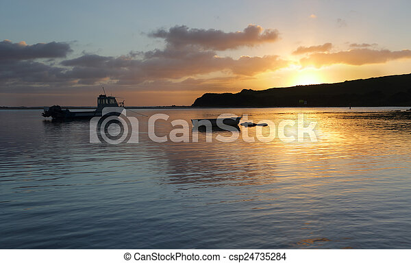 Boats on the water at sunrise - csp24735284