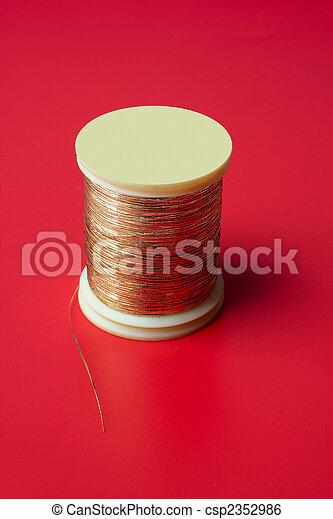bobbin of golden thread on a red background - csp2352986