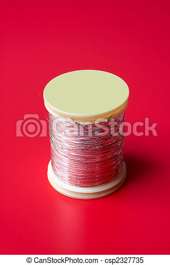 bobbin of thread on a red background - csp2327735