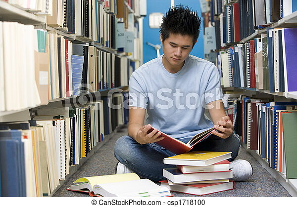Ein Mann, der in Bücherei auf dem Boden sitzt - csp1718100
