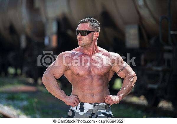 Body Builder Posing At The Railroad - csp16594352