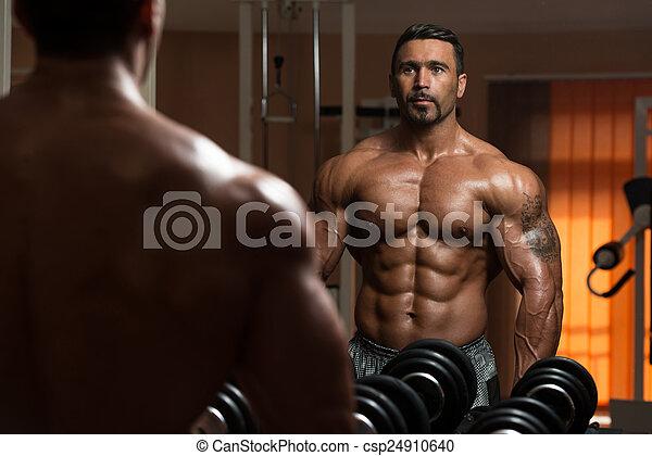 Bodybuilder Exercising Biceps - csp24910640