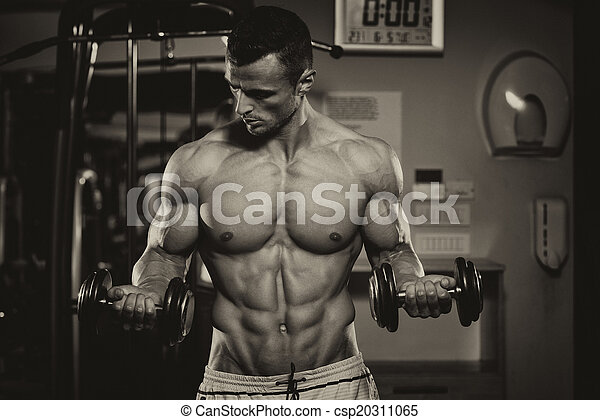 Bodybuilder Exercising Biceps With Dumbbells - csp20311065