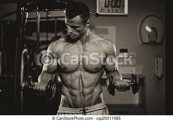 Bodybuilder Exercising Biceps With Dumbbells - csp20311065