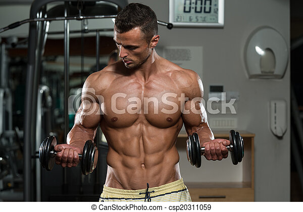 Bodybuilder Exercising Biceps With Dumbbells - csp20311059