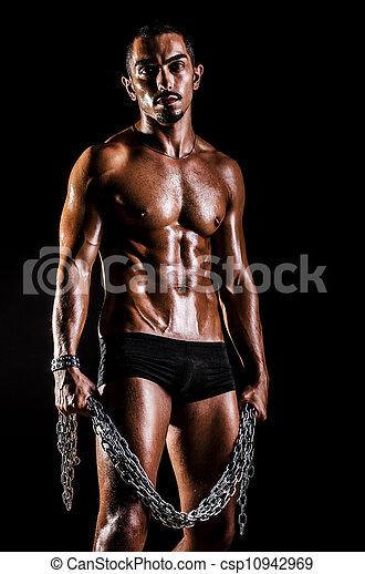 Bodybuilder with chains in dark - csp10942969