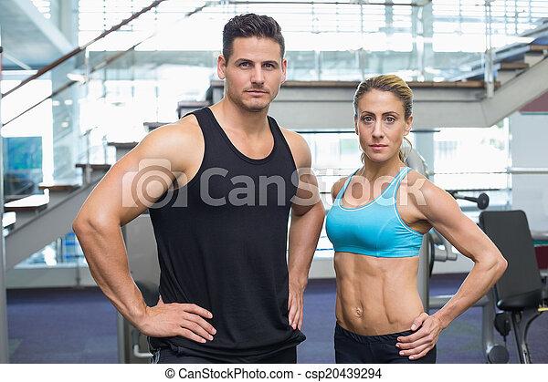 Bodybuilding man and woman frowning at camera - csp20439294