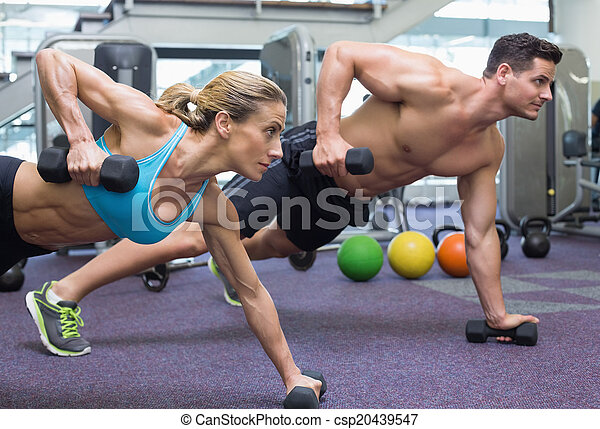 Bodybuilding man and woman holding dumbbells in plank position - csp20439547