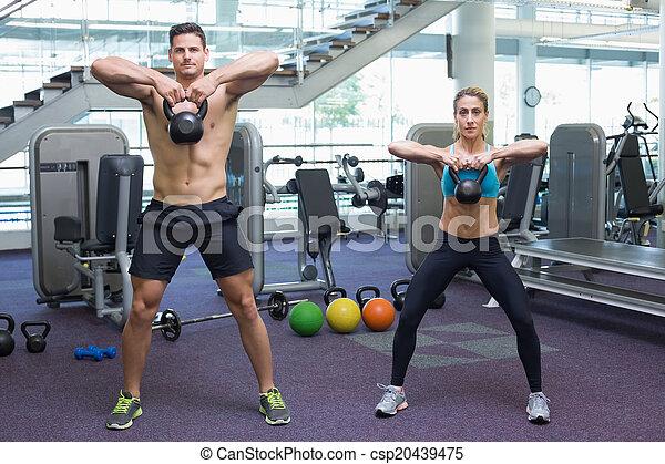 Bodybuilding man and woman lifting kettlebells  - csp20439475
