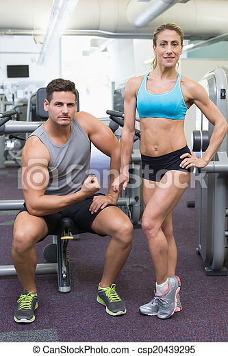 Bodybuilding man and woman posing for the camera - csp20439295