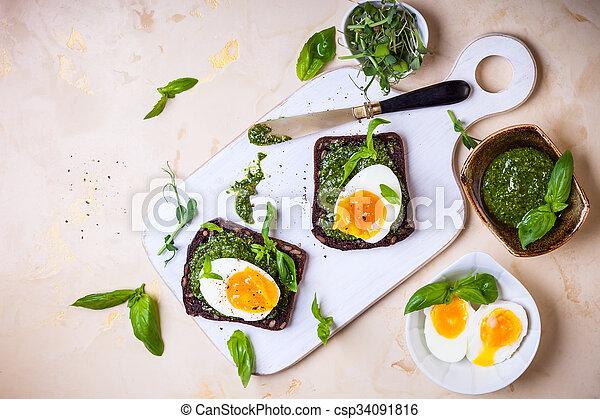 Boiled egg with pesto on toast - csp34091816