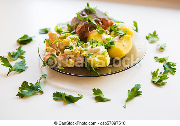 Boiled potatoes under sour cream, red fish, salad sprinkled with parsley on a plate of dark glass - csp57097510