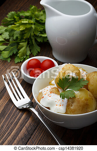 Boiled potatoes with cherry tomatoes, parsley and sour cream on wooden table - csp14381920