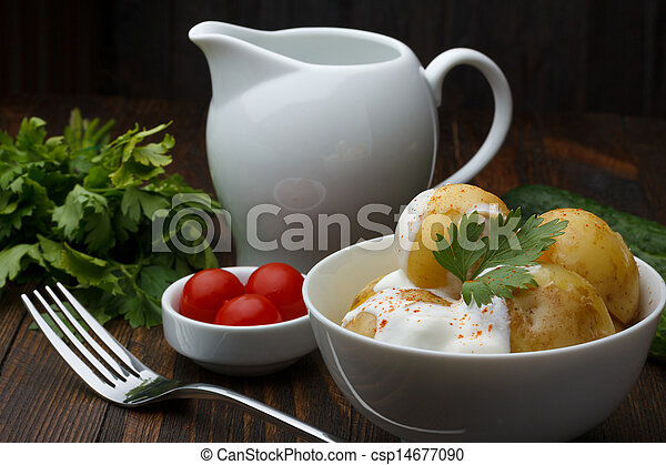 Boiled potatoes with cherry tomatoes, parsley and sour cream on wooden table - csp14677090