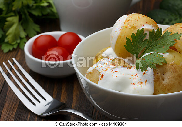 Boiled potatoes with cherry tomatoes, parsley and sour cream on wooden table - csp14409304