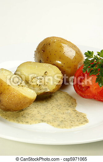 boiled potatoes with parsley sauce on a plate - csp5971065