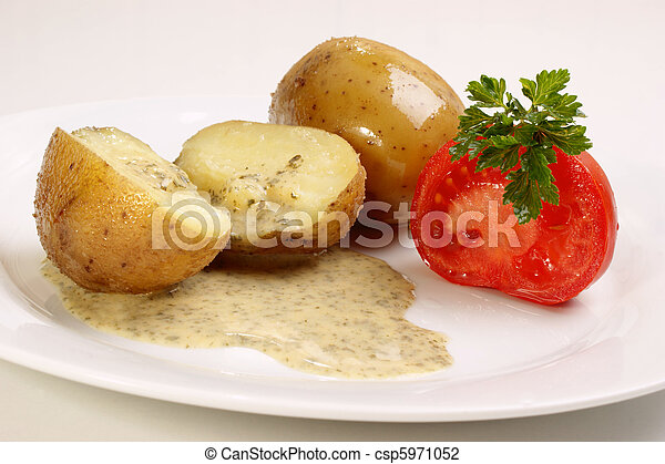 boiled potatoes with parsley sauce on a plate - csp5971052