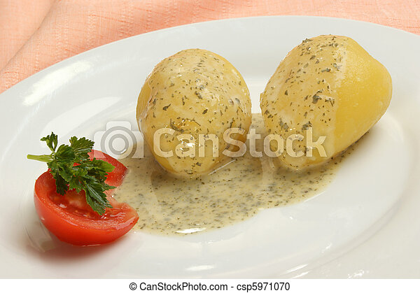 boiled potatoes with parsley sauce on a plate - csp5971070
