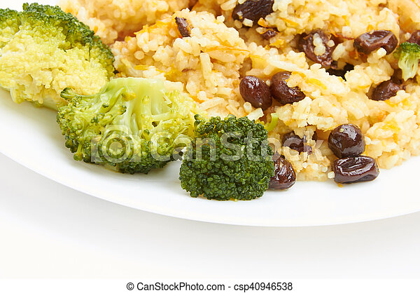 boiled rice with raisins on white plate - csp40946538