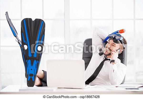 Reservar entradas para las vacaciones. Un apuesto trabajador de oficina en Snorkel y aletas gestando y sonriendo mientras se sienta en su lugar de trabajo - csp18667428