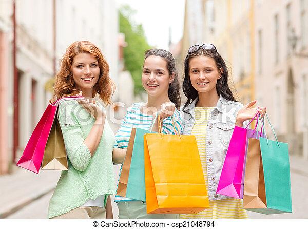 Chicas sonrientes adolescentes con bolsas de compras en la calle - csp21048794
