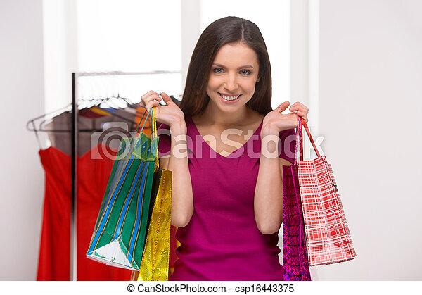 La mujer de la tienda. Una joven alegre sosteniendo bolsas de compras y sonriendo - csp16443375