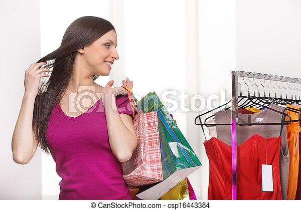 Una tienda de ventas. Una joven alegre con bolsas de compras mirando los vestidos en la tienda - csp16443384