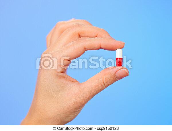 Bolo rojo y blanco (capsule) en mano de doctor, macro vista - csp9150128