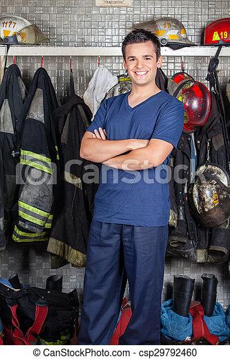 Bombero feliz parado en la estación de bomberos - csp29792460